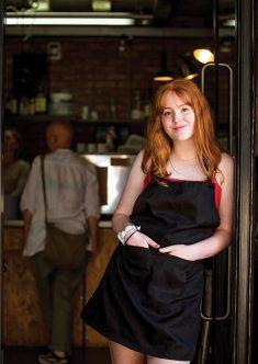 Girl standing in doorway of cafe